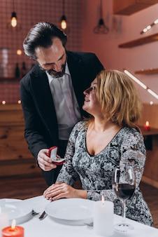 L'homme se tient à côté d'une femme dans un restaurant et lui montre une boîte avec une alliance