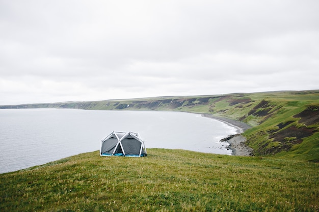 L'homme se tient à côté d'une tente moderne en islande