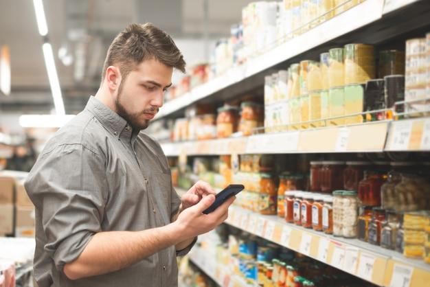 L'homme se tient dans l'allée du supermarché sur des étagères avec des légumes en conserve et utilise un smartphone
