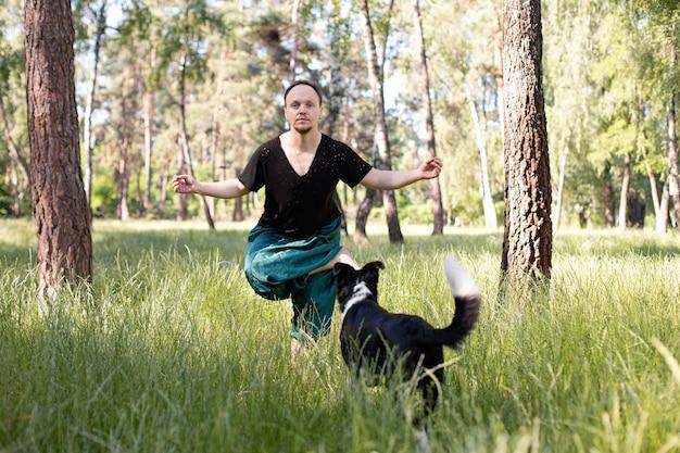 L'homme se tient dans un asana pratiquant le yoga dans la nature avec son chien. journée internationale du yoga