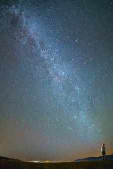 L'homme se tient dans le contexte de la voie lactée. la nuit