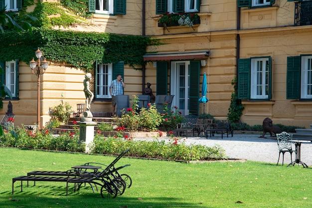 Un homme se tient dans la cour d'une maison de luxe et parle au téléphone.