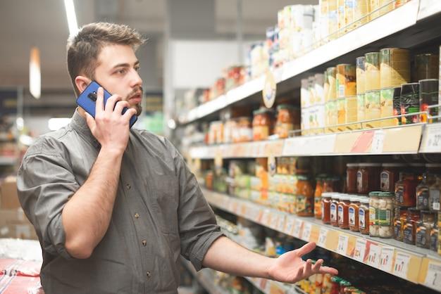L'homme se tient dans le département des légumes en conserve dans le supermarché et appelle au téléphone