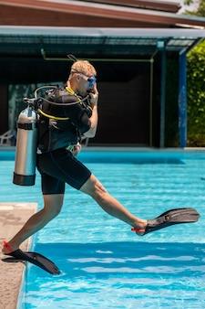 Un homme se tient dans un équipement de plongée et est prêt à plonger sous l'eau dans la piscine