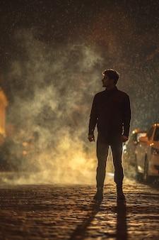 L'homme se tient dans la rue enfumée. le soir la nuit. prise de vue au téléobjectif