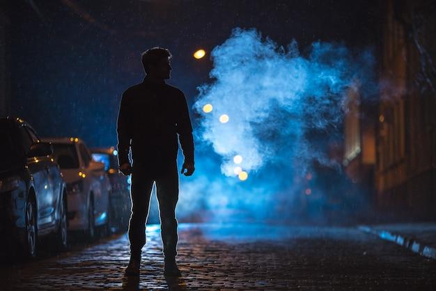 L'homme se tient dans la rue des fumées. le soir la nuit. prise de vue au téléobjectif
