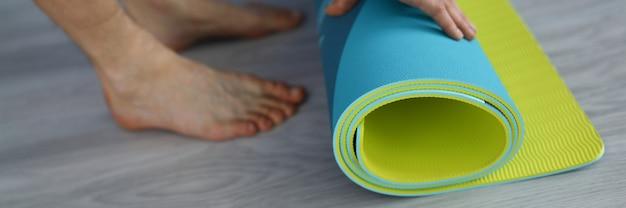 L'homme se tient debout sur le sol et roule sur un tapis de gymnastique multicolore avec ses mains