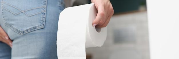 L'homme se tient devant les toilettes et tient du papier toilette