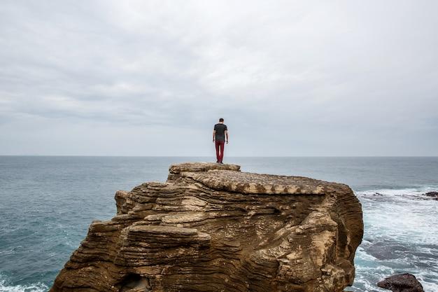 L'homme se tient sur une falaise à la recherche au loin