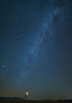 L'homme se tient sur le fond du ciel étoilé. la nuit