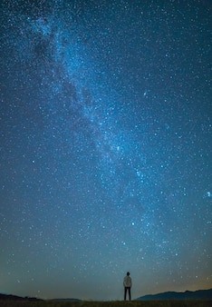L'homme se tient sur le fond des étoiles dans le ciel. la nuit