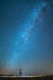 L'homme se tient sur le fond des étoiles. la nuit
