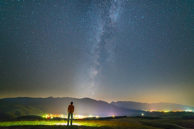 L'homme se tient sur le fond des lumières de la ville. la nuit