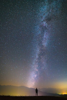 L'homme se tient sur le fond de la voie lactée. la nuit