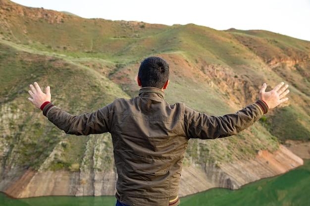 Un homme se tient les mains ouvertes sur une falaise au bord du lac