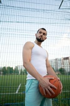 Un homme se tient près d'une clôture dans la rue, tenant un ballon de basket à la main