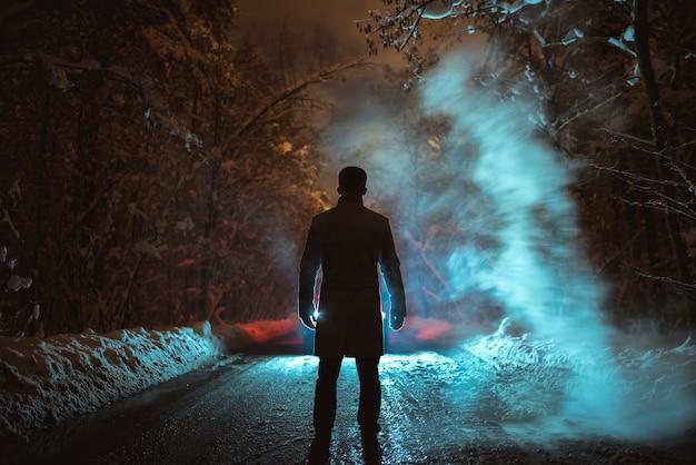 L'homme se tient près de la fumée sur la route forestière. le soir la nuit