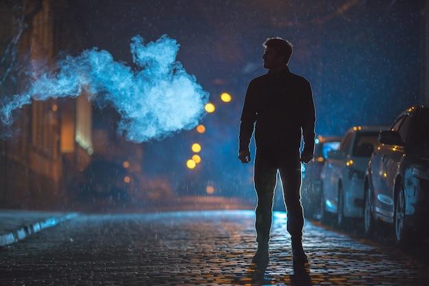 L'homme se tient près de la fumée. le soir la nuit. prise de vue au téléobjectif