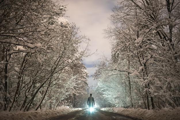 L'homme se tient sur la route enneigée sur le fond clair