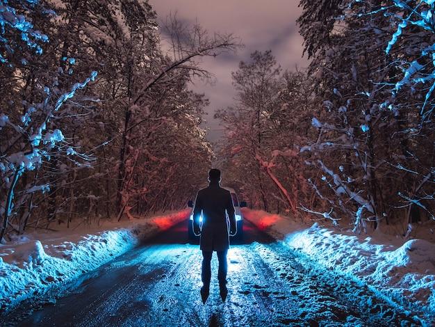 L'homme se tient sur la route forestière près de la voiture. le soir la nuit