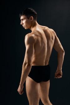 L'homme se tient avec son dos sur un mur sombre