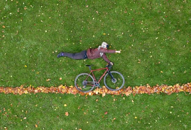 L'homme se trouve sur l'herbe verte avec des feuilles d'automne dans une pose de super-héros avec un vélo.