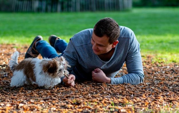 Homme se vautrer dans un parc sur des cônes avec un beau chiot interagissant avec un animal