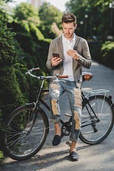 Homme, séance, vélo, holing, jetable, café, tasse, utilisation, téléphone portable