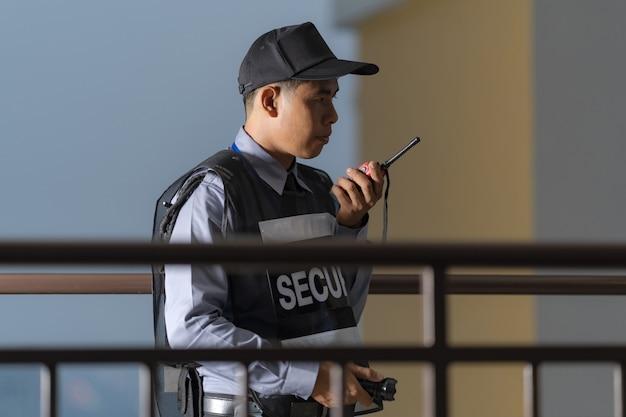 Homme sécurité, debout, dehors, utilisation, radio portative