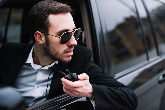 Homme de sécurité grand angle en voiture
