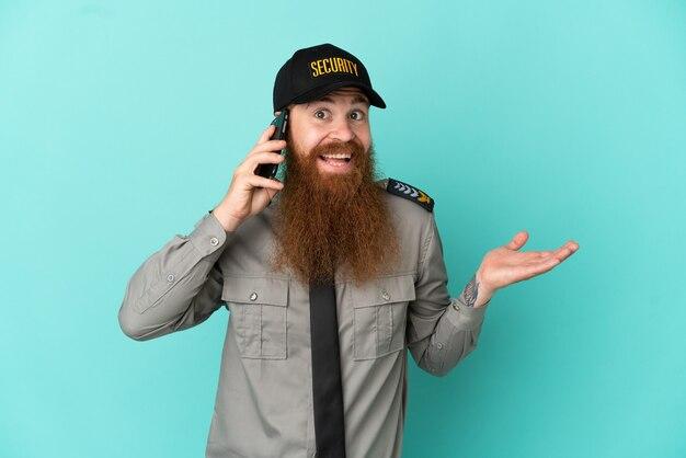 Homme de sécurité rousse isolé sur fond blanc gardant une conversation avec le téléphone portable avec quelqu'un