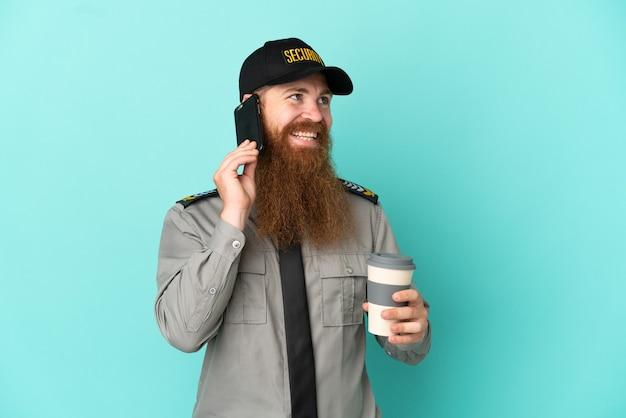 Homme de sécurité rousse isolé sur fond blanc tenant du café à emporter et un mobile
