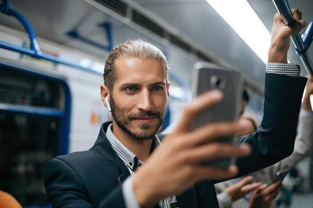 Homme séduisant à l'aide de son smartphone dans la rame de métro