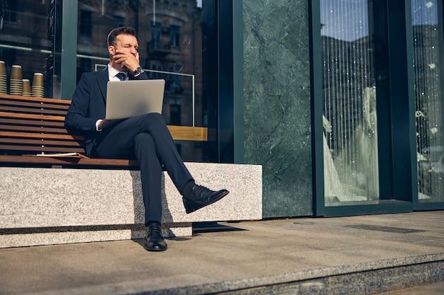 Homme séduisant assis sur un banc seul tout en utilisant un ordinateur portable sur ses genoux et en bâillant