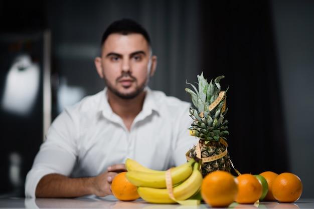 Homme séduisant, assis à une table sur laquelle se trouvent des fruits frais.