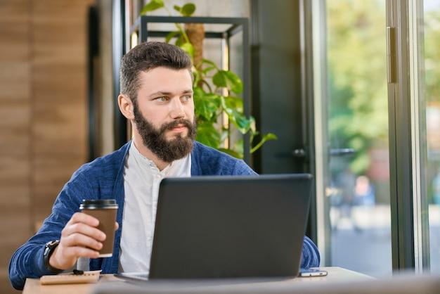 Homme séduisant aux yeux bleu et la barbe travaillant avec un ordinateur portable.