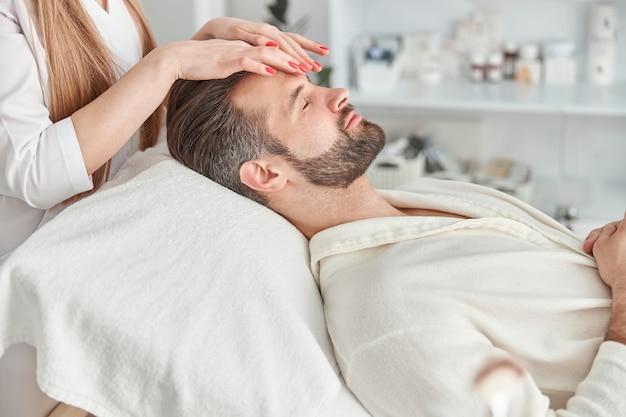 Un homme séduisant avec une barbe est allongé sur le dos, se fait masser le visage soin de beauté de massage du visage. concept de bien-être, de beauté et de relaxation.