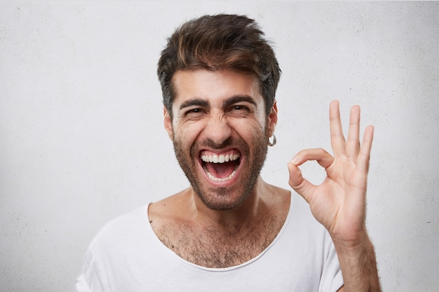Homme séduisant avec barbe fermant les yeux et ouvrant la bouche avec joie montrant signe ok être heureux