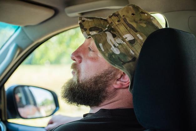 Homme séduisant en bonne voiture. homme avec une barbe dans une voiture. le gars est un passager dans la voiture sur le siège avant.