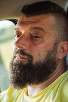Homme séduisant en bonne voiture. homme avec une barbe dans une voiture. un homme barbu dans une voiture ne conduit pas.