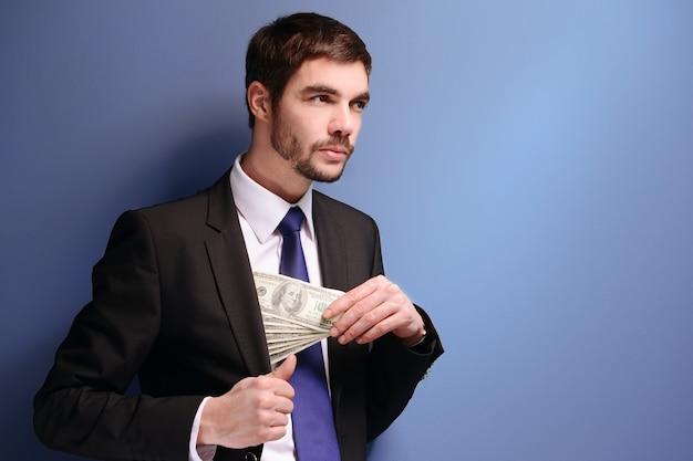 Homme séduisant cachant des billets en dollars en costume sur bleu