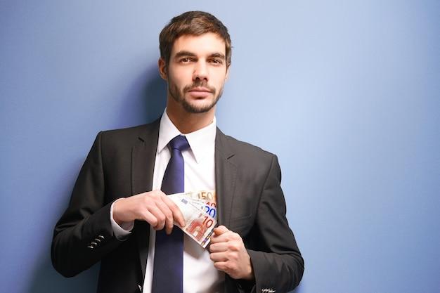 Homme séduisant cachant les billets en euros en costume sur bleu