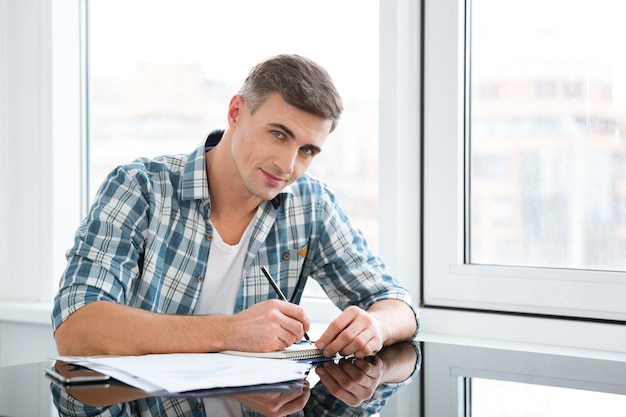 Homme séduisant en chemise à carreaux assis et travaillant au bureau