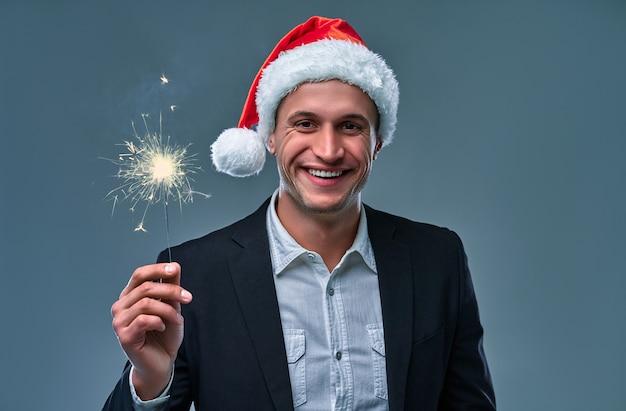 Un homme séduisant avec des cierges magiques célèbre le nouvel an. prise de vue en studio sur fond gris.
