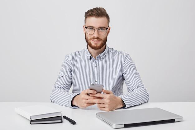 Homme séduisant avec une coiffure à la mode et une barbe rougeâtre épaisse, porte des lunettes arrondies et une chemise formelle,