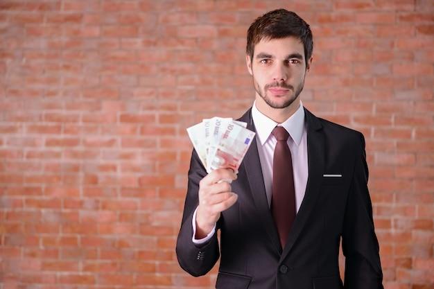 Homme séduisant dans un costume tenant fan de billets en euros sur fond de mur de brique