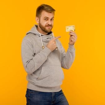 Homme séduisant dans un sweat à capuche gris pointe un doigt sur la carte de crédit qui tient dans sa main sur un fond jaune - image