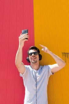 Un homme séduisant avec des écouteurs fait un selfie avec son téléphone portable