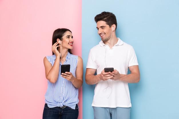 Homme séduisant et femme portant des écouteurs et à l'aide de smartphones, isolés sur un mur coloré