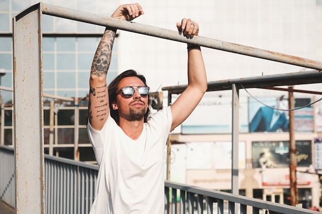 Homme séduisant avec des lunettes de soleil traîner dans la ville